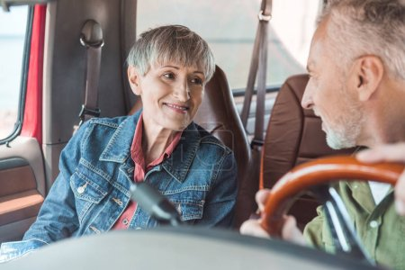 Photo for Senior couple looking at each other while sitting in car - Royalty Free Image