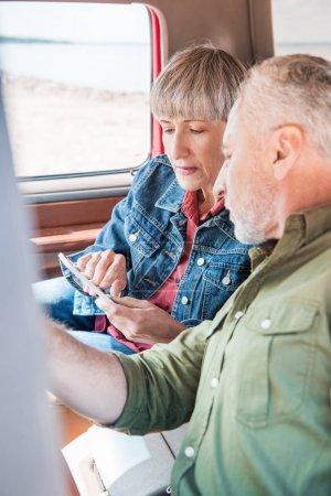 Seniorenpaar nutzt Smartphone im Auto bei sonnigem Tag