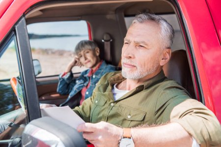 Photo for Senior man holding map while sitting in car with wife - Royalty Free Image