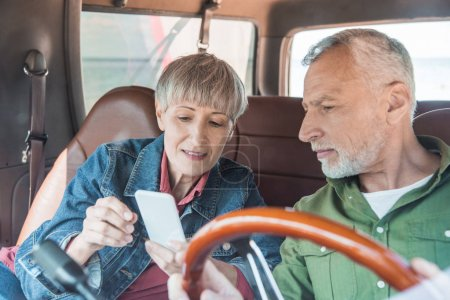 Photo for Senior couple using smartphone in car in sunny day - Royalty Free Image