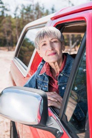 Photo pour Senior femme en jean veste regardant par la fenêtre de la voiture - image libre de droit