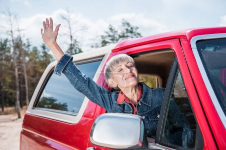 Photo for Happy senior woman waving hand from car window with closed eyes - Royalty Free Image