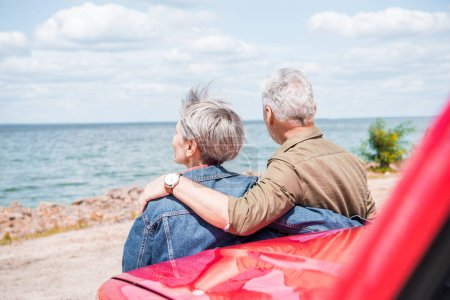 Photo for Back view of senior couple standing near red car and embracing at beach - Royalty Free Image