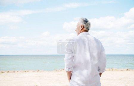 Photo pour Vue arrière de l'homme aîné dans la chemise blanche à la plage dans le jour ensoleillé - image libre de droit