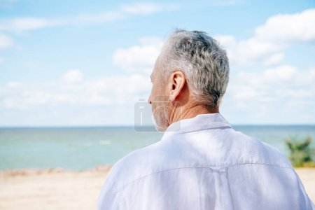 Photo for Back view of senior man in white shirt at beach in sunny day - Royalty Free Image