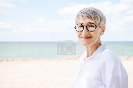 Photo for Smiling senior woman in glasses and white shirt looking at camera at beach - Royalty Free Image