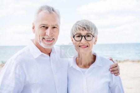 Photo for Front view of smiling senior couple embracing and looking at camera at beach - Royalty Free Image