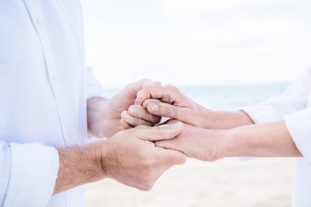 Photo for Cropped view of senior couple in white shirts holding hands under blue sky - Royalty Free Image