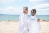 """Постер, картина, фотообои """"задний вид старшей пары в белых рубашках, обнимая на пляже"""""""