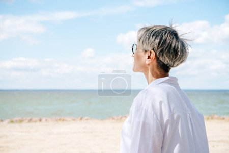 Photo for Senior woman in white shirt looking away at beach - Royalty Free Image