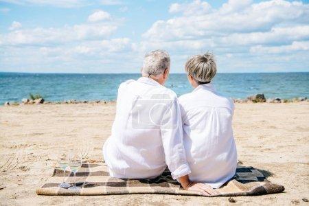 Photo pour Vue arrière du couple aîné dans les chemises blanches s'asseyant sur la couverture à la plage - image libre de droit