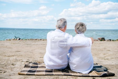 Photo pour Vue arrière du couple aîné dans les chemises blanches s'asseyant sur la couverture et embrassant à la plage - image libre de droit
