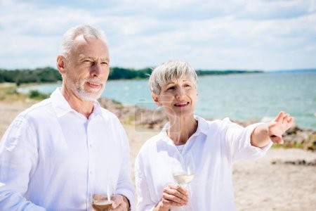 Photo for Smiling senior couple holding wine glasses with wine and looking away at beach - Royalty Free Image