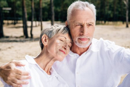 Photo for Senior couple in white shirts embracing in forest in sunny day - Royalty Free Image