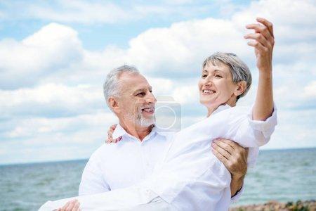 Photo pour Homme aîné de sourire dans la femme de fixation de chemise blanche sous le ciel bleu près de la rivière - image libre de droit