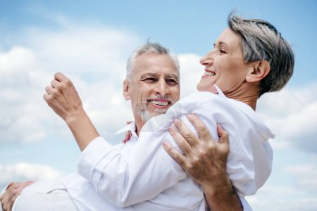 Photo for Smiling senior man in white shirt holding wife under blue sky - Royalty Free Image