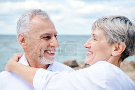smiling senior couple embracing and looking at each other near river