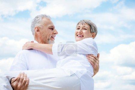 Photo pour Homme âgé souriant en chemise blanche soulevant femme sous le ciel bleu - image libre de droit