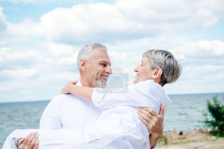 Photo for Smiling senior man in white shirt lifting wife under blue sky - Royalty Free Image