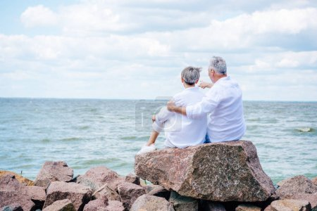 Foto de Back view of senior couple in white shirts embracing near river under blue sky - Imagen libre de derechos