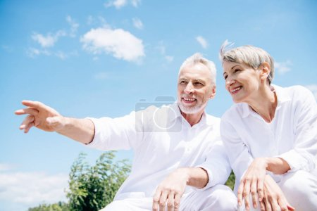 Photo for Happy smiling senior couple in white shirts looking away under blue sky - Royalty Free Image