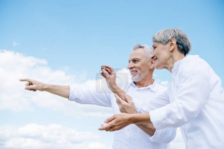Photo for Happy smiling senior couple holding stone and pointing with finger under blue sky - Royalty Free Image