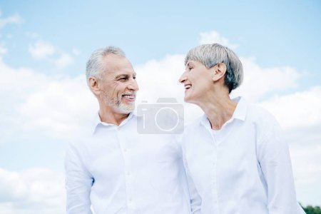 Photo for Happy smiling senior couple in white shirts looking at each other under blue sky - Royalty Free Image