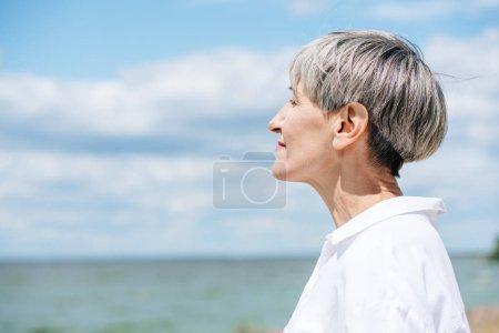 Photo pour Vue latérale de la femme aînée dans la chemise blanche regardant loin près de la rivière dans la journée ensoleillée - image libre de droit