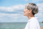 """Постер, картина, фотообои """"вид стороны пожилой женщины в белой рубашке, глядя в сторону возле реки в солнечный день"""""""