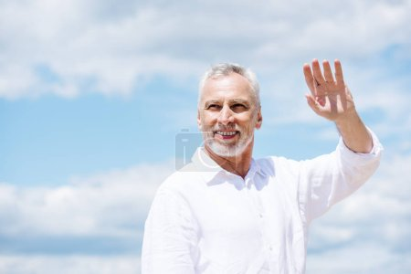 smiling senior man with beard looking away and waving hand under blue sky in sunny day