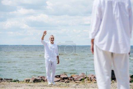 Photo pour Vue recadrée de femme aînée et d'homme agitant la main près de la rivière dans la journée ensoleillée - image libre de droit
