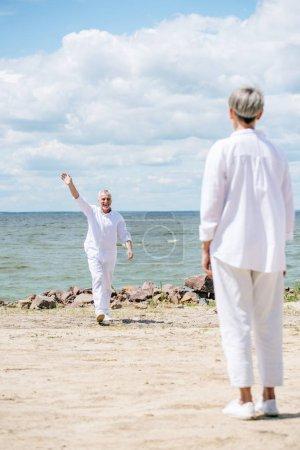 Photo pour Vue arrière de la femme aînée et de l'homme agitant la main près de la rivière dans la journée ensoleillée - image libre de droit