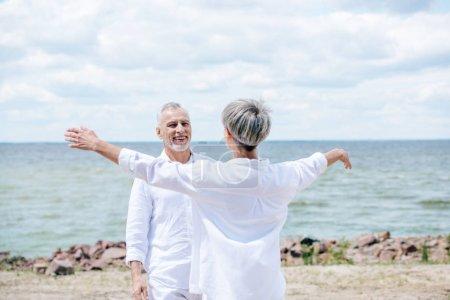 Photo pour Vue arrière de femme aînée embrassant le mari de sourire à la plage - image libre de droit
