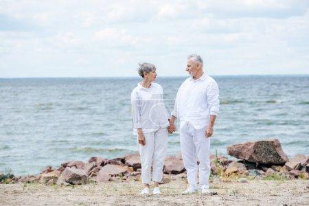 Photo pour Vue pleine longueur de couples aînés se tenant des mains et regardant l'un l'autre à la plage - image libre de droit