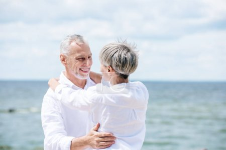 Photo for Happy senior couple in white shirts embracing and looking at each other under blue sky - Royalty Free Image