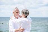 """Постер, картина, фотообои """"счастливая старшая пара в белых рубашках обнимая и глядя друг на друга под голубым небом"""""""