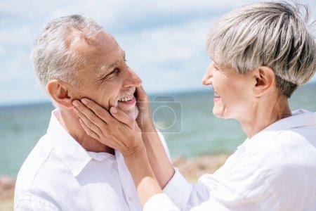 Photo pour Femme aînée heureuse regardant le mari et touchant son visage sous le ciel bleu - image libre de droit