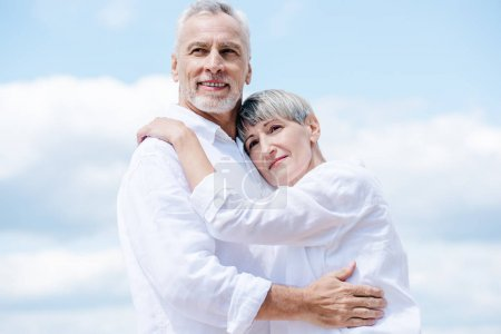 Photo for Happy senior couple in white shirts embracing under blue sky - Royalty Free Image