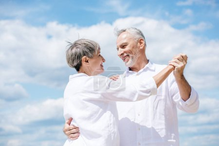 Photo for Happy senior couple looking at each other while dancing under blue sky - Royalty Free Image