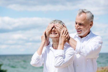 Photo pour Homme aîné souriant couvrant des yeux pour la femme près de la rivière dans le jour ensoleillé - image libre de droit