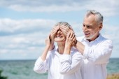 """Постер, картина, фотообои """"улыбающийся старший человек, закрывающий глаза для жены возле реки в солнечный день"""""""