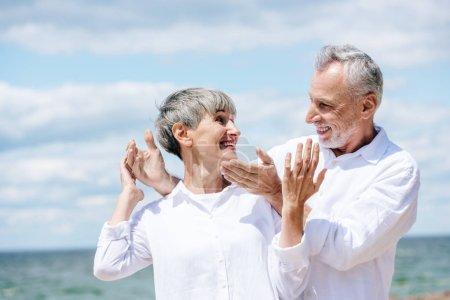 Photo pour Couples aînés heureux dans les chemises blanches restant sous le ciel bleu dans le jour ensoleillé - image libre de droit
