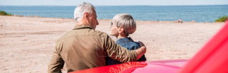 Photo for Panoramic view of senior couple of tourists standing near car and embracing at beach - Royalty Free Image