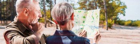 Photo pour Vue panoramique de deux voyageurs aînés regardant la carte dans la forêt - image libre de droit
