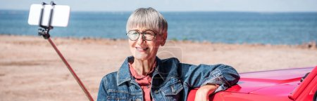 Photo for Panoramic view of smiling senior woman standing near car and taking selfie at beach - Royalty Free Image