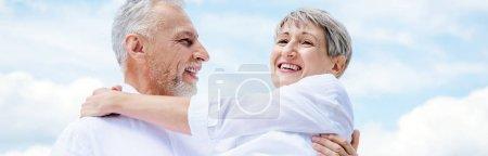 Photo pour Vue panoramique d'un homme âgé souriant soulevant sa femme sous le ciel bleu - image libre de droit