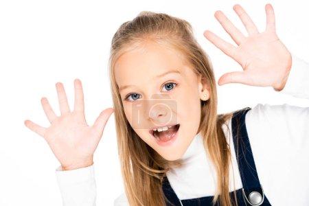 Photo pour Écolière gaie affichant des mains souillées de craie tout en regardant l'appareil-photo d'isolement sur le blanc - image libre de droit