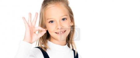 Photo pour Plan panoramique d'écolière souriante montrant un geste correct en regardant la caméra isolée sur blanc - image libre de droit
