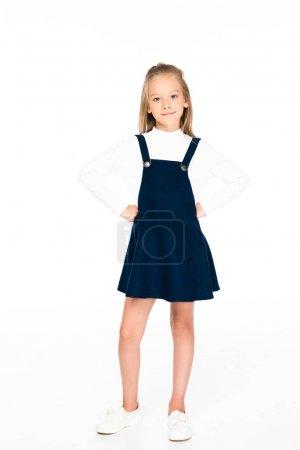 Photo pour Vue pleine longueur de mignonne écolière tenant la main sur les hanches tout en posant à la caméra sur fond blanc - image libre de droit