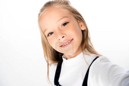 Photo pour Écolière gaie souriant à l'appareil-photo tout en prenant le selfie sur le fond blanc - image libre de droit